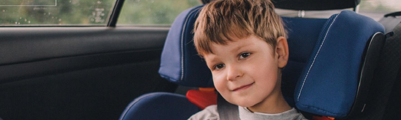 בתמונה- ילד יושב בכיסא בטיחותי חגור חגורת בטיחות